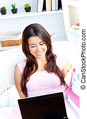 Cheerful asian woman using her laptop after shopping on the sofa in the living-room
