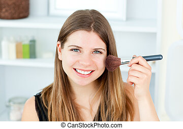 Smiling caucasian woman putting powder on her face smiling at the camera in the bathroom
