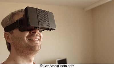 Close up of grey haired man having fun using his mobile phone VR headset at home. Virtual reality mask in action. 4K steadicam video