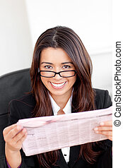 Charming asian businesswoman holiding a newspaper smiling at...