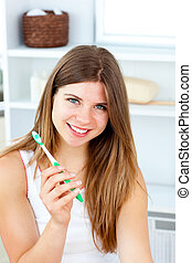 Delighted woman holding a toothbrush smiling at the camera
