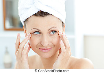 Smiling young woman putting moisturizer on her face