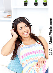 Radiant asian young woman listen to music with headphones on the couch smiling at the camera