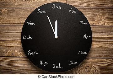Black round clock calendar. 12 months. Wooden background