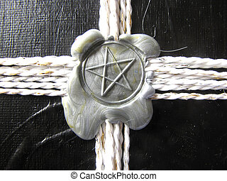 a seal of pentagram on black cover - A gray seal of...