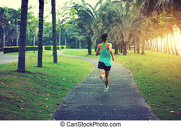 healthy lifestyle young sporty asian woman running at tropical park