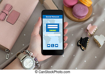 female hand with jewelry and watch holding phone social...