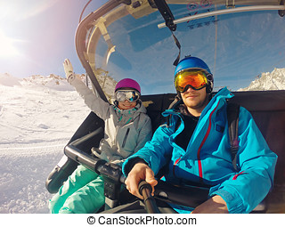 happy couple taking selfie in chairlift at ski resort