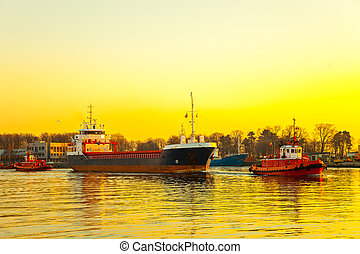 Tugboats and ship - Tugboats assisting cargo ship in port at...