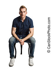 Man in blue shirt and jeans sitting down - A sad man sitting...