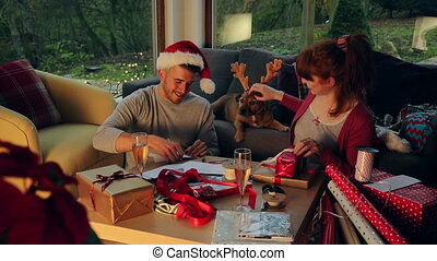 Santa's Little Helper - Young couple at home with their pet...