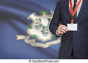 Businessman holding badge on a lanyard with USA state flag on background - Connecticut