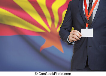 Businessman holding badge on a lanyard with USA state flag on background - Arizona