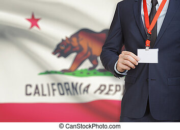 Businessman holding badge on a lanyard with USA state flag...