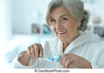 Senior woman brushing her teeth - Portrait of happy senior...