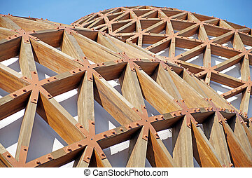 Detail of a modern wooden architecture in glued laminated timber on blue sky