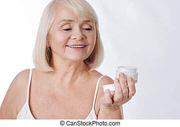 Pleasant senior woman looking at the cream bottle - Moisture...