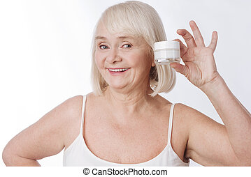 Cheerful senior woman holding a cream bottle - Taking away...