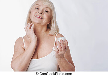 Pleasant nice woman fighting with age - Skin care. Pleasant...