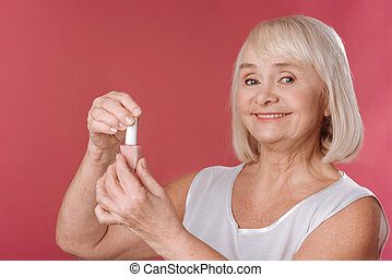 Pleasant good looking woman opening nail varnish - Beautiful...
