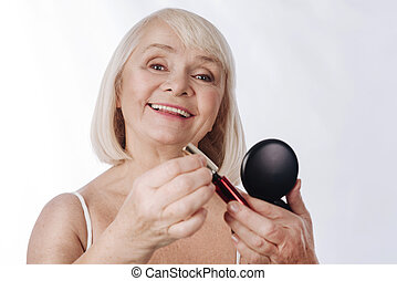 Cheerful positive woman putting on mascara