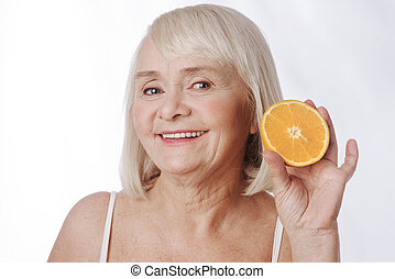 Cheerful positive woman holding a citrus fruit