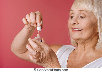 Content retired woman using nail varnish - Home manicure....