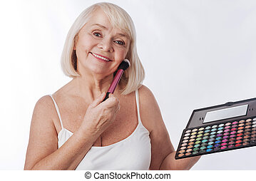 Joyful retired woman holding an eyeshadow palette -...