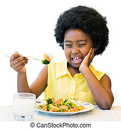 African kid pulling ugly face at dinner table.