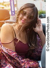 Happy brunette girl sitting and smiling in the back seat of...