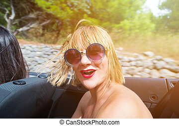Happy blonde wearing sunglasses sitting and smiling in the...