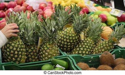 man picks fruit pineapple in the supermarket