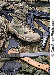 One army boot and different weapon.Selective focus -...