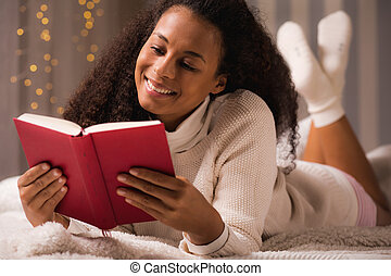 Relaxing with her favourite book - Shot of a smiling young...