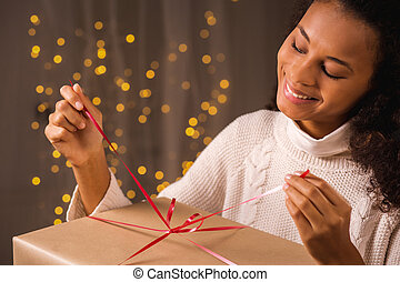 Unwrapping Christmas present - Shot of a young woman...