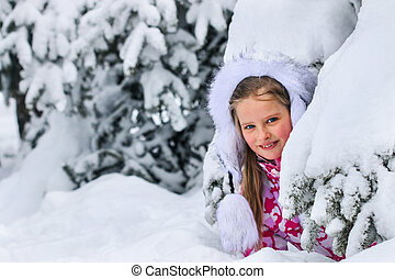Portrait of little kid girl in winter clothes plying in deep...