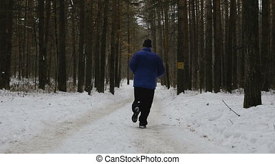male runner running on winter trail in pine forest