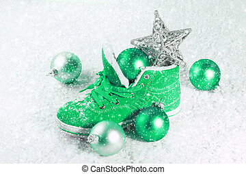 Green shoe with Christmas decorations in the snow. Christmas...