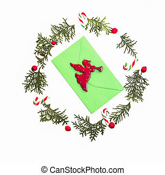 Christmas wreath made of thuja twigs, red wild rose fruits with green envelop and Xmas decoration cane in the middle. White background. Top view, flat lay.