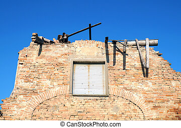 Old ruined brick fence isolated on blue sky background .