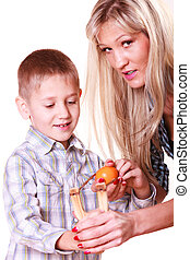 Boy with mother hold sling shot and mandarine. - Nature and...