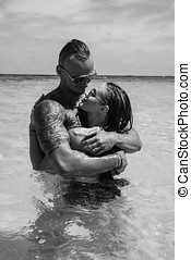 Attractive young couple in the sea - Sensual young topless...
