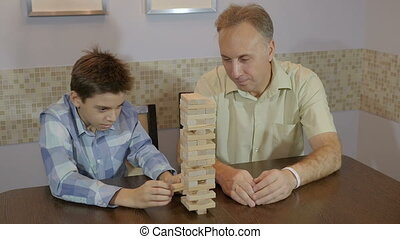 Dad and son playing board game Jenga