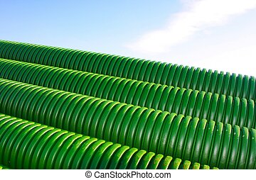 Stack of green tubes at a building site