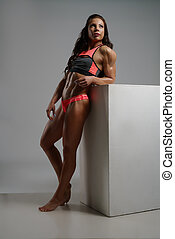 Full length photo of female bodybuilder posing at camera