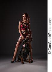 Erotica. Domineering mistress posing with doberman -...