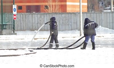 Making ice skating - two man pouring water from a hose and...