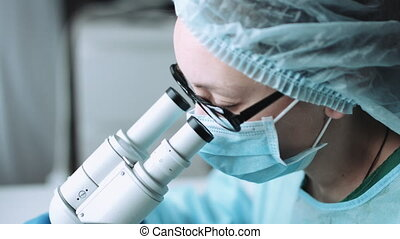 Scientist working in laboratory with microscope