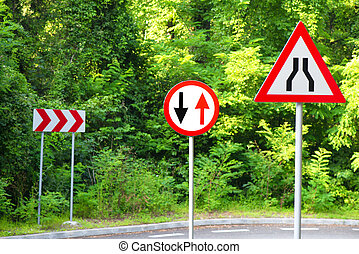 Traffic signs on a road near forest