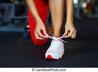 Running shoes - woman tying shoe laces. Closeup of fitness...